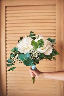 Weibliche hand, die schönen und stilvollen pastellhochzeitsblumenstrauß hält
