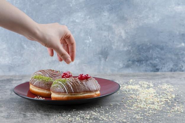 Weibliche hand, die schokoladenkrapfen mit beere und streuseln von der marmoroberfläche nimmt.