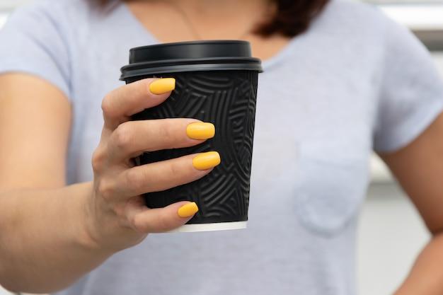 Weibliche hand, die schwarze papierschale mit kaffee zum mitnehmen hält