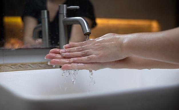 Weibliche hand, die seife in der spüle auftragen oder antibakteriell ist