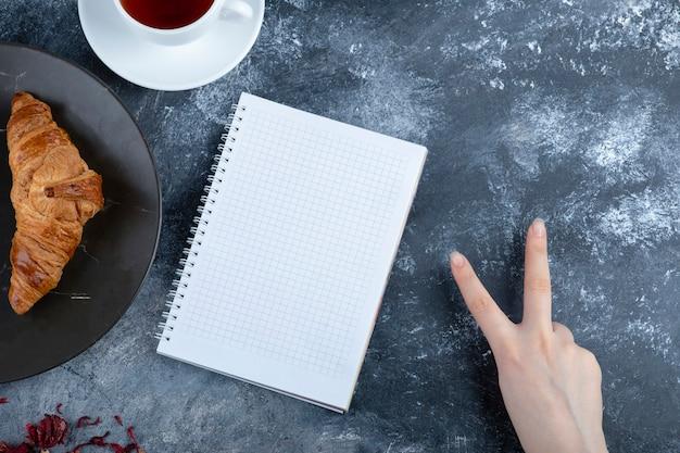 Weibliche hand, die siegeszeichen nahe frischem croissant zeigt, geöffnetes notizbuch und tasse tee.