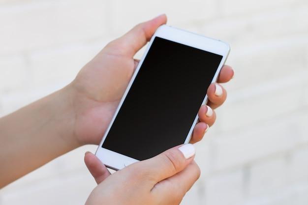 Weibliche hand, die smartphone auf weißem backsteinmauerhintergrund hält