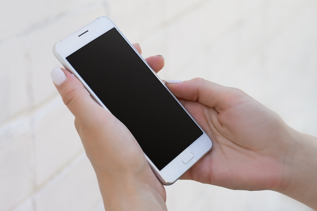 Weibliche hand, die smartphone auf weißem backsteinmauerhintergrund, modell mit kopienraum hält