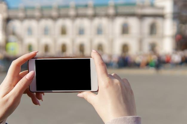 Weibliche hand, die smartphone hält, nehmen fotomasse.