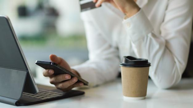 Weibliche hand, die smartphone hält, während sie ein digitales tablet auf dem tisch mit pappbecher verwendet