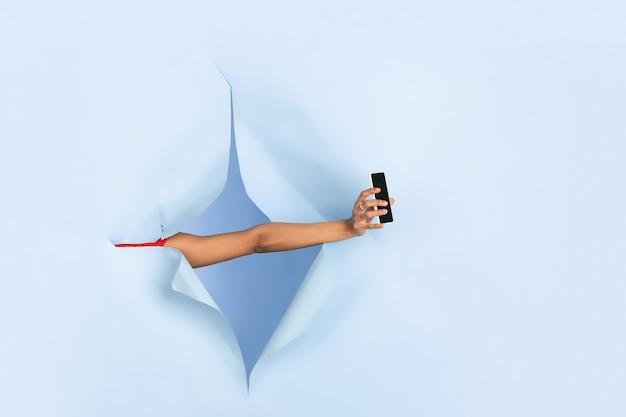Weibliche hand, die smartphone im zerrissenen blauen papierlochhintergrund gibt. aufbruch, durchbruch mit gestikulieren. konzept der feier, einkaufen, vorschlag, verkauf, anzeige. exemplar. aktionen, rabatte.
