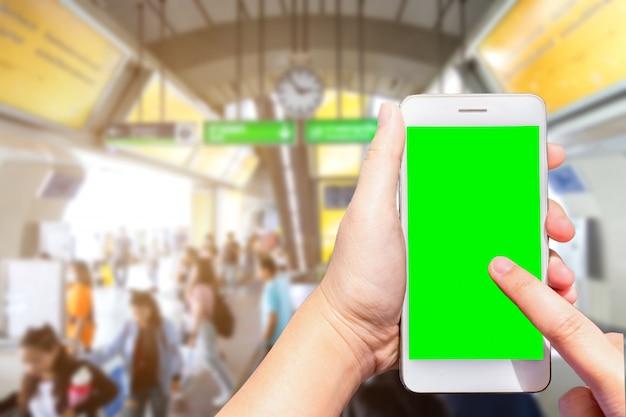 Weibliche hand, die smartphone mit unscharfen bildern des leeren bildschirms hält, berühren abstrakte unschärfe in der bts skytrain station in bangkok