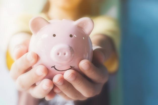Weibliche hand, die sparschwein hält. sparen sie geld und geld