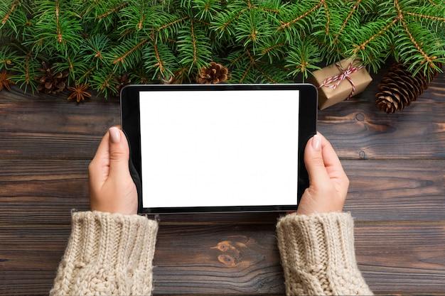 Weibliche hand, die tablette, perspektivenansicht, winterurlaubverkäufe, weihnachtseinkaufen hält