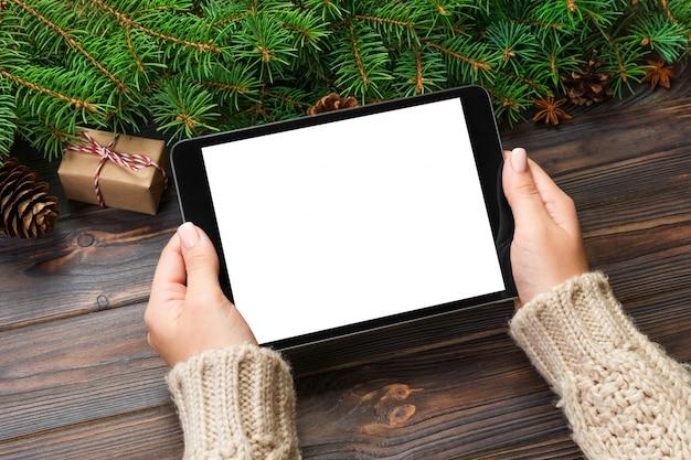 Weibliche hand, die tablette winterurlaubverkäufe hält