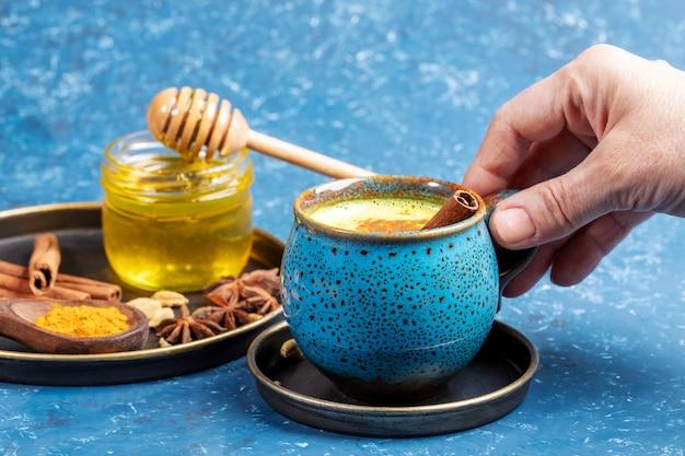 Weibliche hand, die tasse des traditionellen ayurvedischen getränks goldene kurkuma-milch und teller mit seinen bestandteilen auf blau hält.