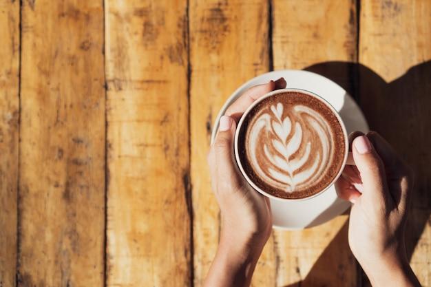 Weibliche hand, die tasse heißen kakao oder schokolade auf holztisch, nah oben hält