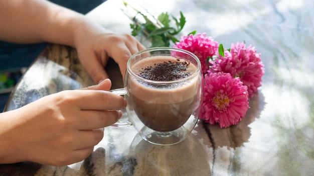 Weibliche hand, die tasse kakao oder heiße schokolade neben blumen auf marmortisch hält