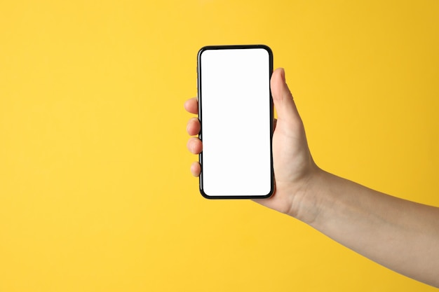 Weibliche hand, die telefon mit leerem bildschirm auf gelber oberfläche hält