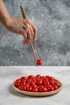 Weibliche hand, die tomate mit stäbchen vom hölzernen teller nimmt.