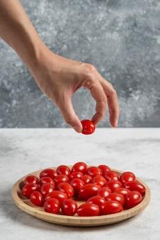 Weibliche hand, die tomate vom hölzernen teller nimmt.