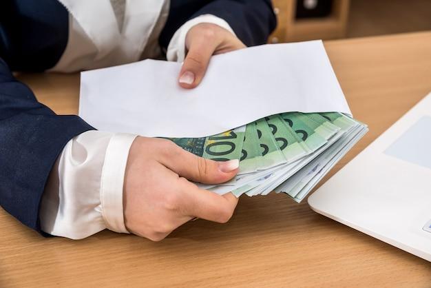 Weibliche hand, die umschlag mit euro-geld hält. geldkonzept
