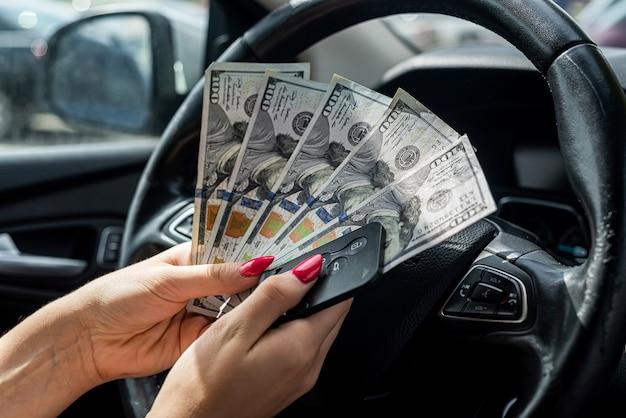 Weibliche hand, die us-dollar in einem auto zählt, konzept des kaufs oder der miete von autos
