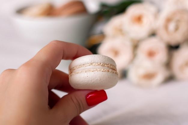 Weibliche hand, die vanille-makrone auf weißem rosenhintergrund hält