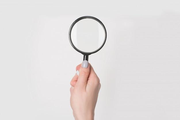 Weibliche hand, die vergrößerungsglas lokalisiert hält