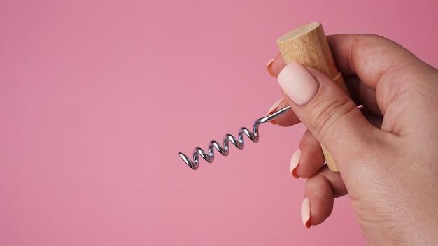 Weibliche hand, die vintage-korkenzieher-flaschenöffner über rosa hintergrund hält