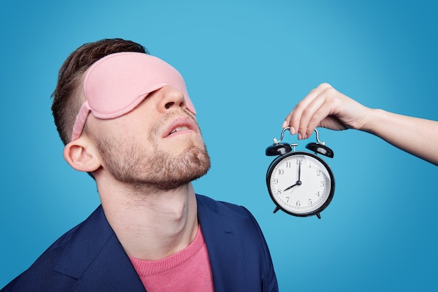 Weibliche hand, die wecker nahe an jungem mann mit schlafmaske auf seinen augen beim nickerchen hält