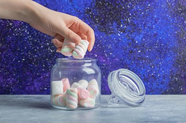 Weibliche hand, die weiche bunte marshmallows aus dem glas nimmt