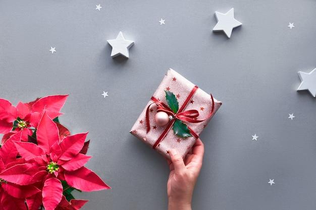 Weibliche hand, die weihnachtsgeschenk hält, eingewickelt in metallisch rosa geschenkpapier mit rotem band, stechpalmenblatt und kugel. weihnachtsdekor.