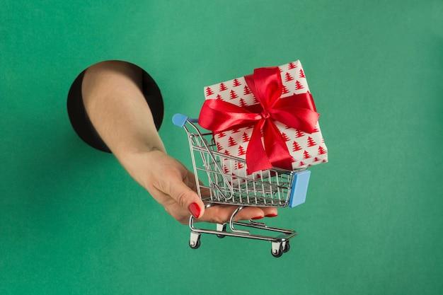 Weibliche hand, die weihnachtsgeschenkbox durch rundes loch im grünbuch hält.
