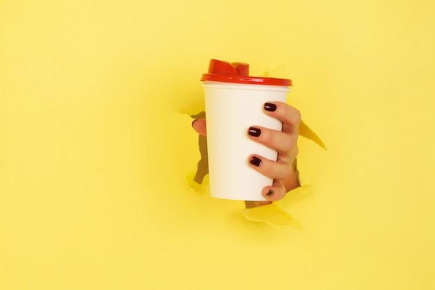 Weibliche hand, die weißbuchbecher auf gelbem hintergrund hält.