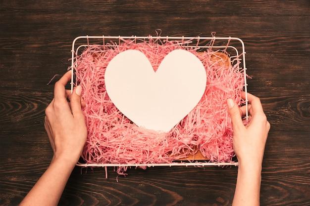 Weibliche hand, die weißbuchherz für valentinsgrußtag hält