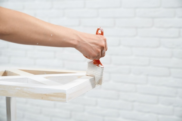 Weibliche hand, die weiße farbe auf lagerständer aufträgt
