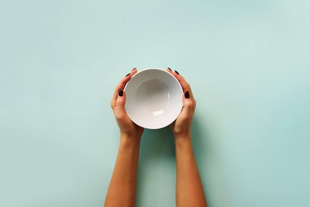 Weibliche hand, die weiße leere schüssel auf blauem hintergrund mit kopienraum hält.