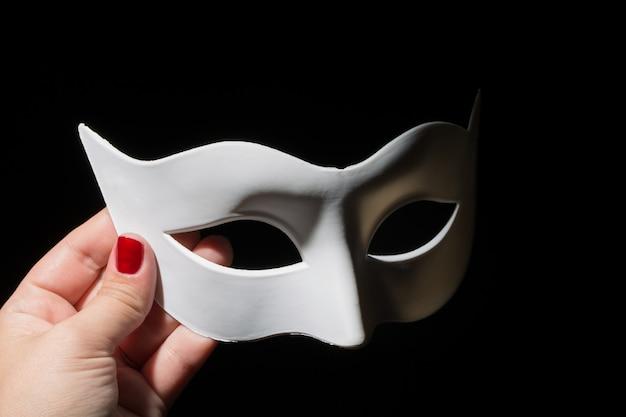 Weibliche hand, die weiße plastikmaske auf schwarzem hält