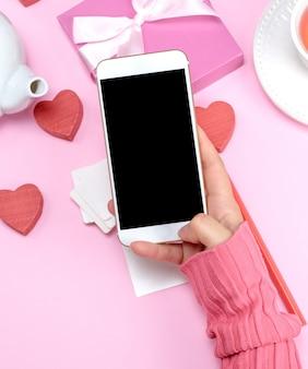 Weibliche hand, die weißes intelligentes telefon mit leerem schwarzem schirm hält