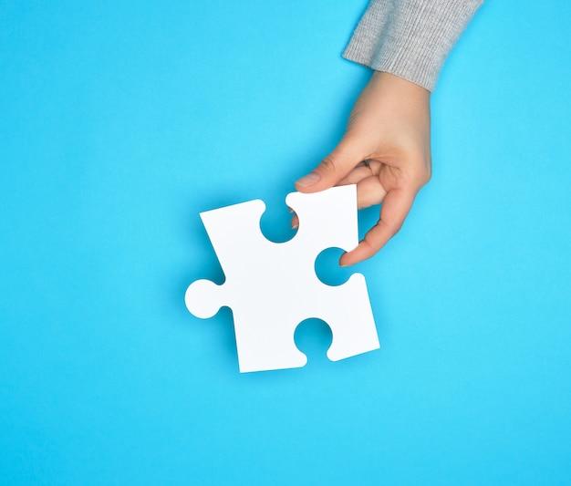 Weibliche hand, die weißes leeres papierpuzzlespiel, blauen hintergrund hält