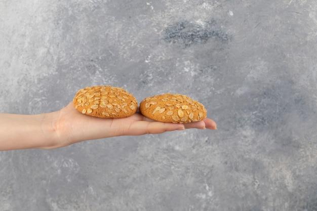 Weibliche hand, die zwei haferkekse auf marmoroberfläche hält