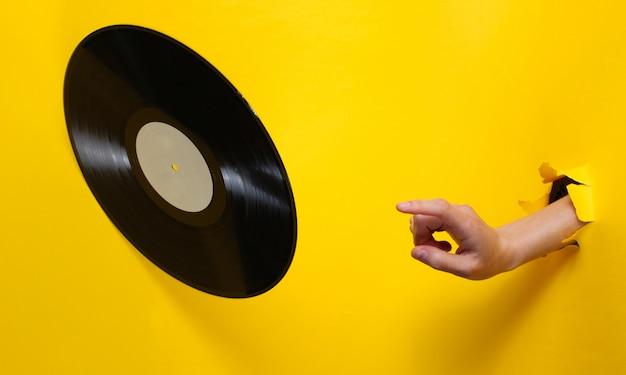 Weibliche hand dreht schallplatte durch zerrissenes gelbes papier. minimalistisches retro-konzept