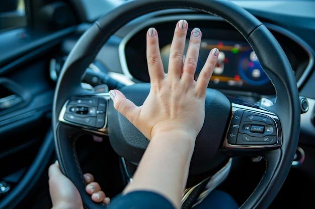 Weibliche hand drückt die hupe am lenkrad eines modernen autos. kein gesicht