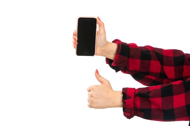 Weibliche hand einer vorderansicht im schwarzroten karierten hemd, das smartphone auf dem weiß hält