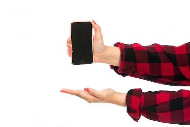 Weibliche hand einer vorderansicht im schwarzroten karierten hemd, das smartphone hält, das offene handfläche auf dem weiß zeigt