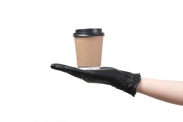 Weibliche hand einer vorderansicht in schwarzen handschuhen, die kaffeetasse auf weiß halten