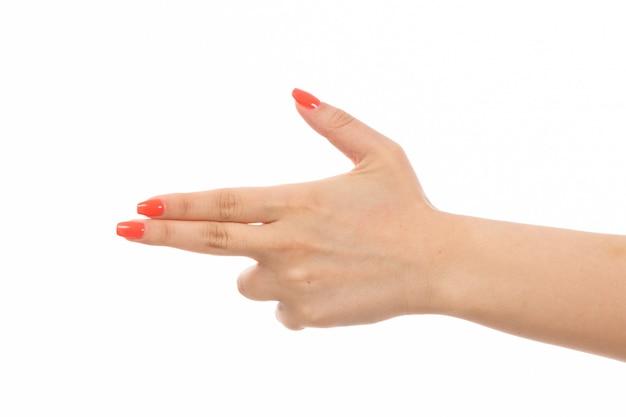 Weibliche hand einer vorderansicht mit farbigen nägeln, die pistolenhaltung auf dem weiß zeigen