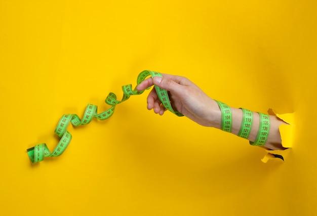 Weibliche hand, eingewickelt in ein lineal durch zerrissenes gelbes papier. minimalistisches gewichtsverlustkonzept