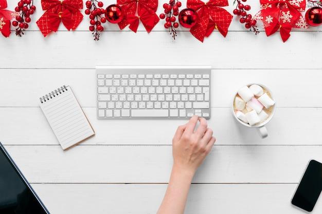 Weibliche hand. frau, die an einem bürotisch mit weihnachtsfestlichen dekorationen arbeitet