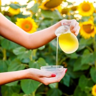 Weibliche hand gießt sonnenblumenöl aus einem krug in eine schüssel