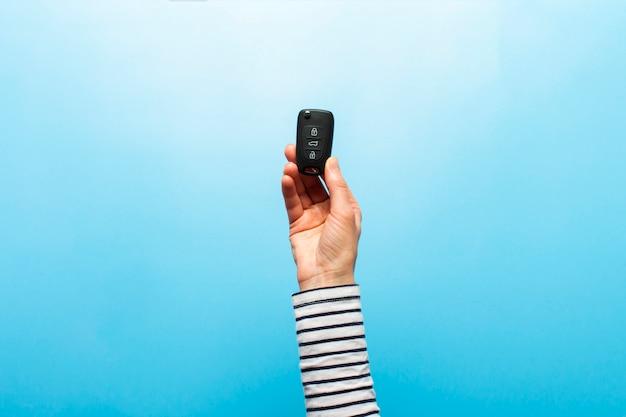 Weibliche hand hält autoschlüssel auf einem blauen hintergrund. konzeptauto, mietwagen, geschenk, fahrunterricht, führerschein.