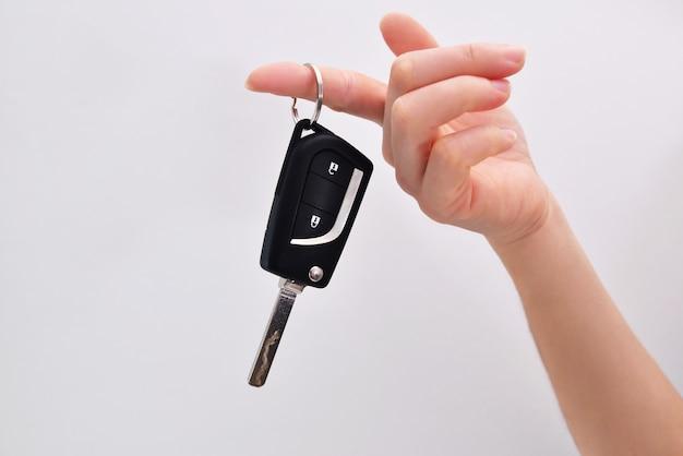 Weibliche hand hält autoschlüssel. nahansicht. weißer hintergrund. autoschlüssel an einem finger.