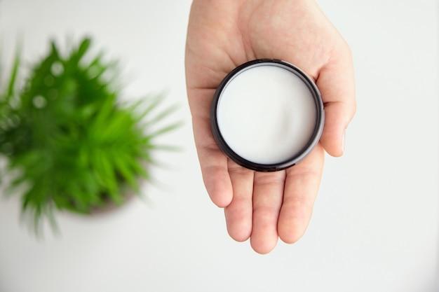 Weibliche hand hält behälter mit weißer anti-aging-glättungs- und beruhigungscreme