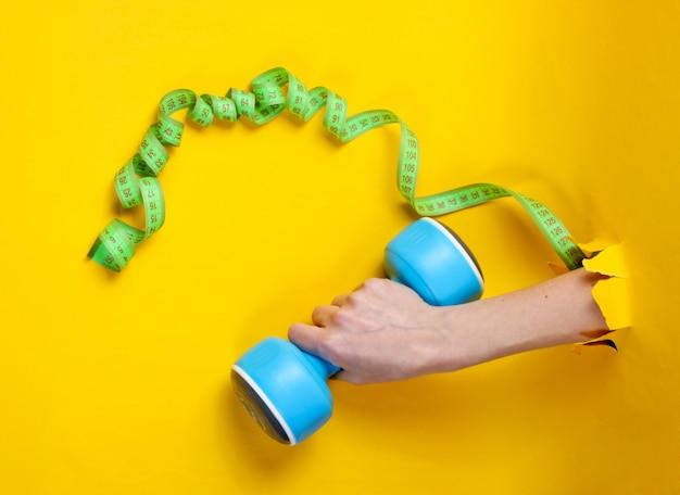 Weibliche hand hält blaue plastikhantel, herrscher durch zerrissenes gelbes papier. minimalistisches fitnesskonzept